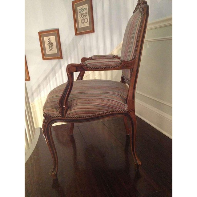 Pair of French walnut upholstered armchairs with cabriole legs, carved backs and apron, upholstered arms and brass...