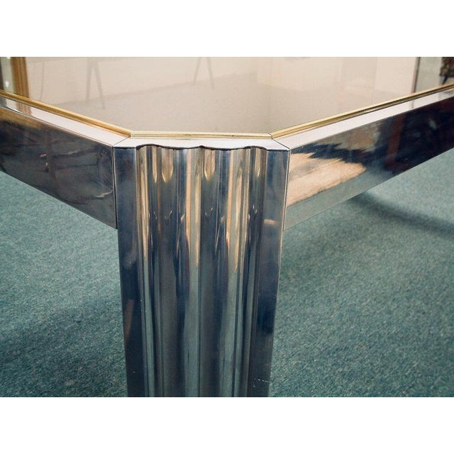 A very sleek and sophisticated polished aluminum and gold anodized aluminum dining table of riveted construction with a...