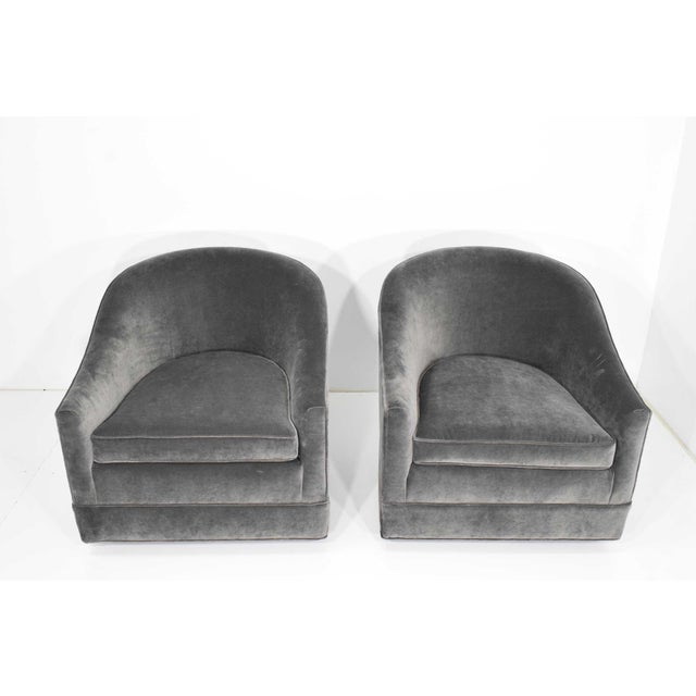 Chairs are upholstered in a gray velvet. They swivel and have a black base. They are super comfortable and a good size.