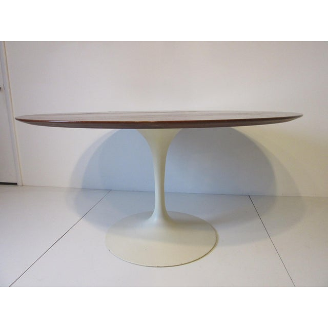 A walnut beveled edged dining table with off white metal tulip base designed by Eero Saarinen for the Knoll Furniture...