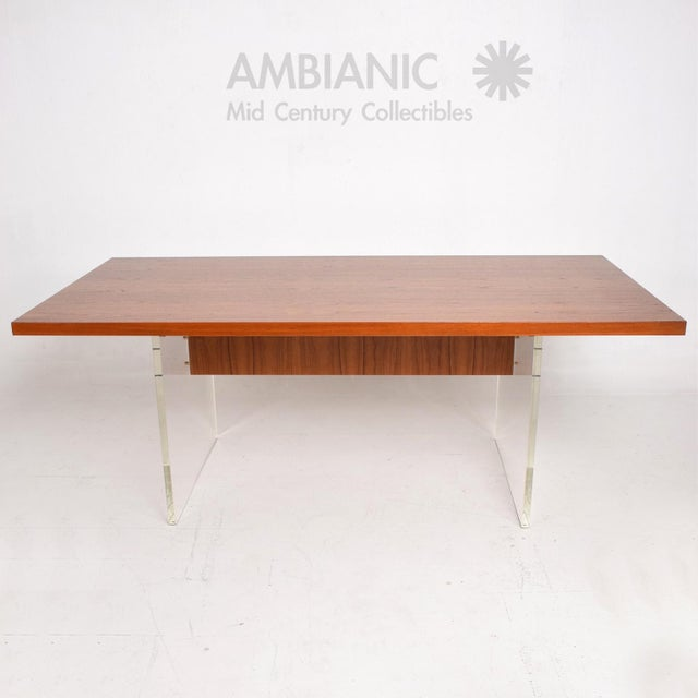 For your consideration a beautiful dining table or work table in teak wood with Lucite legs. Solid brass hardware. Lucite...