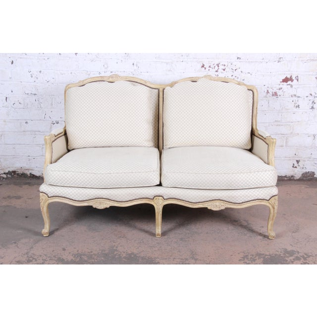 A gorgeous French Provincial Louis XV style loveseat or settee by Baker Furniture. The loveseat features stunning carved...