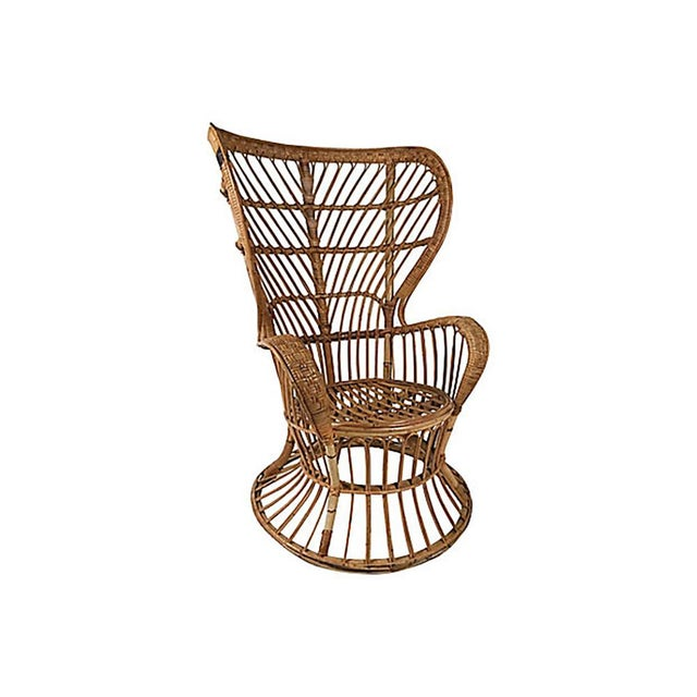 Italian Mid Century Modern rattan wingback chair by Lio Carminati for Vittorio Bonacina Como, circa 1950s. The architect...