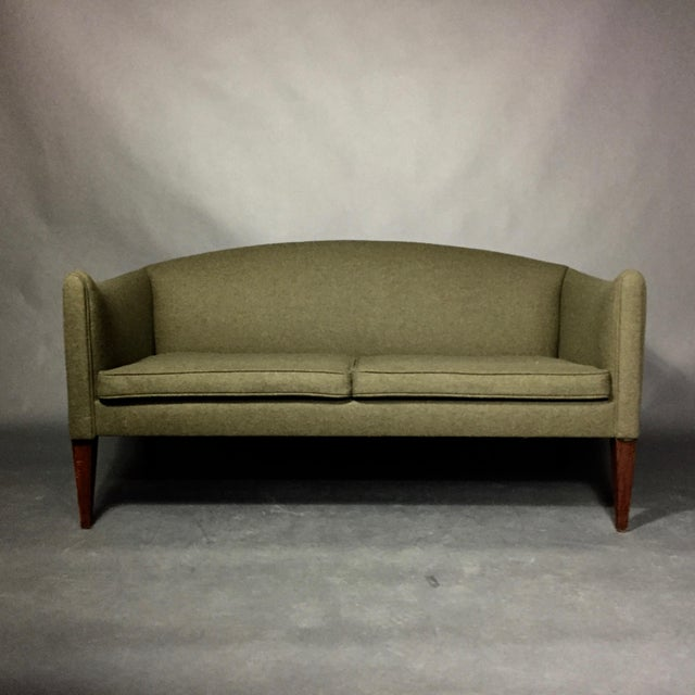 The sleek modernism of Scandinavian design by Illum Wikkelsø - this 2-seat sofa has curved arms and back, recently...