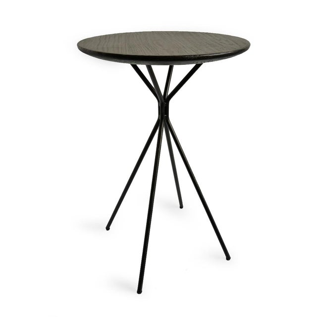 Modern black side table with unique design iron base and round wood top. Great piece for any style interior. Each may vary...