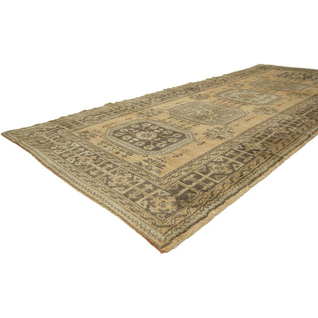 This hand-knotted wool vintage Turkish Oushak runner features five amulet medallions filled with roundels and floral...