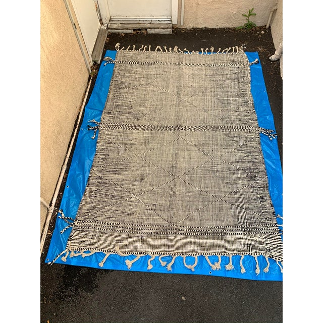 Black and white woven Moroccan rug with criss cross diamond design and tassel fringe on sides and ends. This neutral toned...