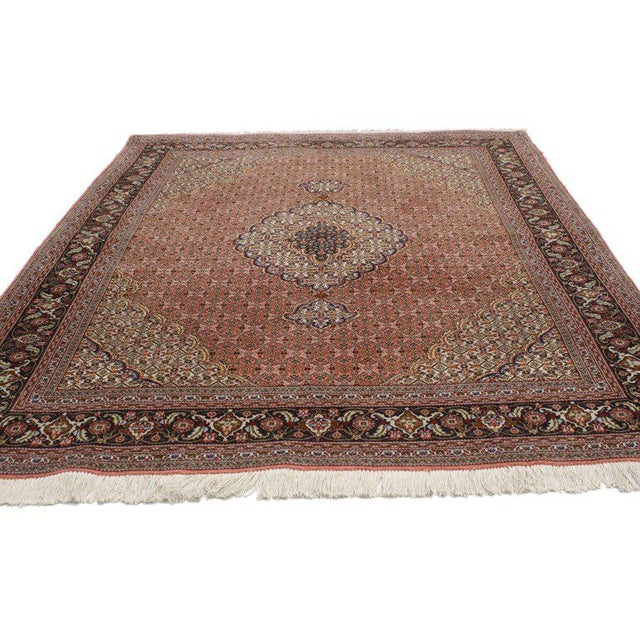 This hand-knotted wool vintage Persian Tabriz rug features a centre medallion with an all-over pattern surrounded by a...
