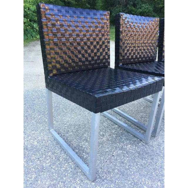 Black woven chairs made by Tidelli with a solid gray base. Minor imperfections from use but overall good condition.