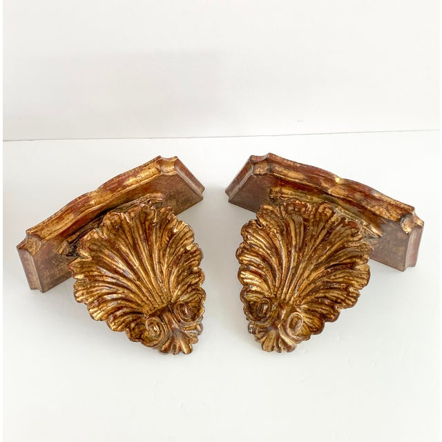 Vintage Florentine style gilt carved wood wall shelf sconce in the form of a shell. A pair. 2 hooks on the back to hang...