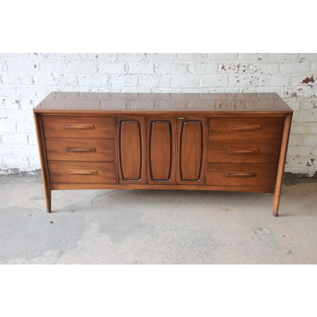 Offering a very nice Broyhill Emphasis mid-century modern sculpted walnut credenza or triple dresser. The credenza has...