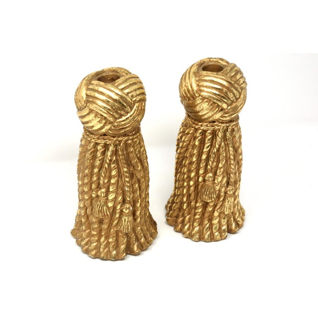 A pair of vintage gold-colored plaster candlesticks, with a rope and tassel design. There are some small chips - see...