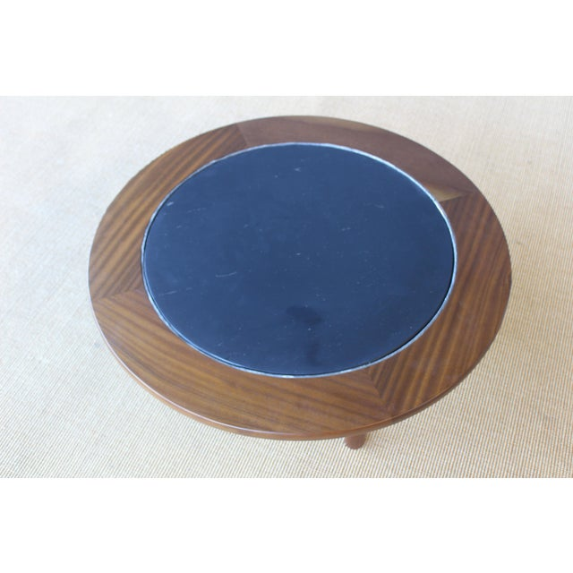 Mahogany coffee table with a slate inserted top. France, 1960s. Base has been recently refinished. Slate top shows some...
