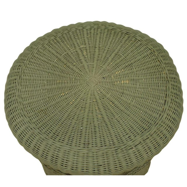This is a vintage painted wicker parlor table. Light tea to celadon green paint color, this table features a round top...