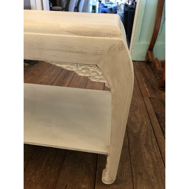 An unusual and chic rectangular two tier side table having an antiqued whitewashed finish, slightly curved silhouette, and...