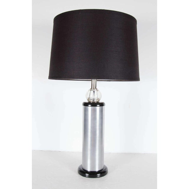 This very sophisticated lamps features a base of ebonized walnut with a cylinder of brushed aluminum with another ebonized...