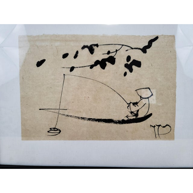 Japanese sumi ink drawing in black frame. Beautiful loose, minimal strokes suggest a fisherman under cherry blossom trees....