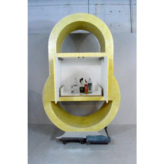 Extremely cool yellow rattan-covered postmodern bar or TV cabinet with a chrome metal covered base. It has a shelf inside...