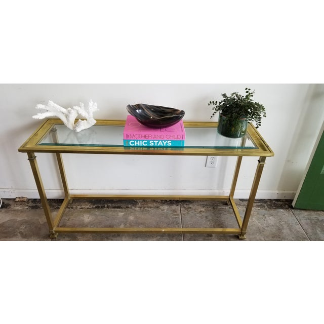 Sleek brass and glass table by Mastercraft. Perfect statement piece in an entry or as sofa table.