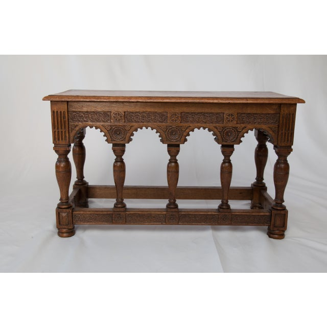 A superb French neo-Gothic style 19th-century oak bench with beveled top, hand-turned bun feet, and hand carved apron....