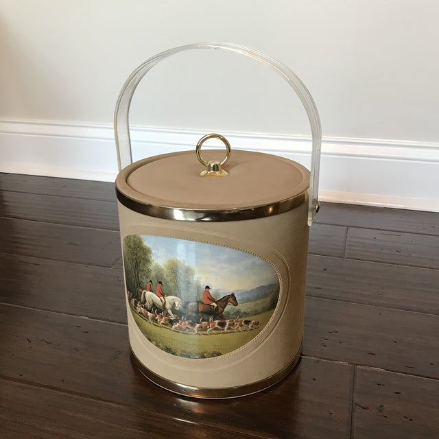 This is a fabulous vintage ice bucket. The piece features a picturesque equestrian scene on velvet with an acrylic handle.