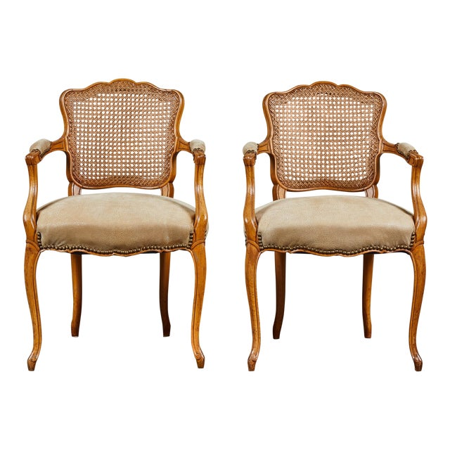 Armchair with caned back and upholstered seat, circa 19th century. Lighter wood tone, with nailhead finishing on arms and...