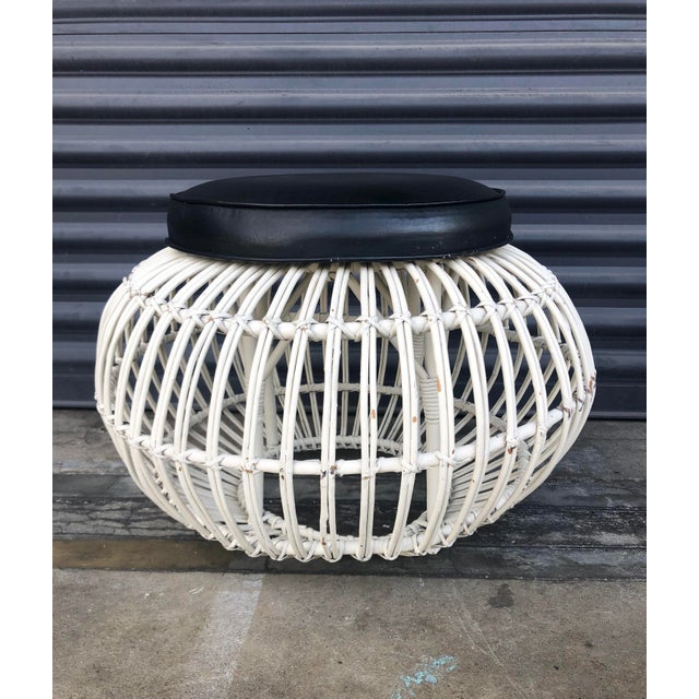 Mid century Franco Albini style pencil reed rattan ottoman. Round pouf shape with upholstered seat attached.