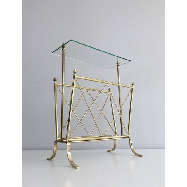 1940s French brass and glass magazine rack attributed to Maison Jansen. This piece is currently in France, please allow 4...