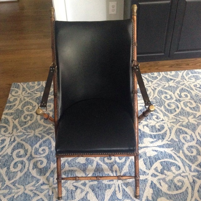 Campaign chair with brass tacks, black vinyl covering, and leather arm rests. Minor cracking in seat, but otherwise good...