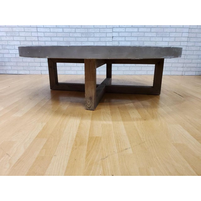 Restoration Hardware Heston round coffee table. Interlocking planes of reclaimed pine support a simple concrete tabletop...