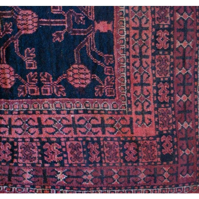 An early 20th century Central Asian Khotan carpet with an all-over pomegranate motif on an indigo background, surrounded...