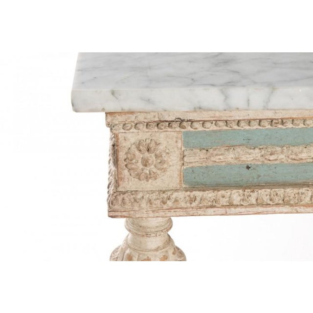Antique Swedish Empire console with original blue paint and stone top. Frieze features pairs of griffins and acanthus leaves.