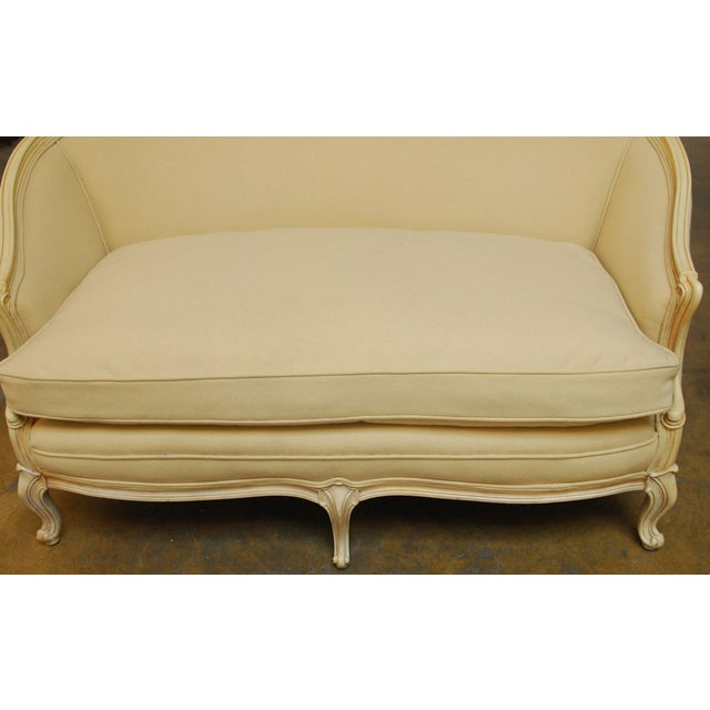 A chic French hand carved settee made in the Louis XV taste. Featuring a cream lacquer frame with cabriole legs and...