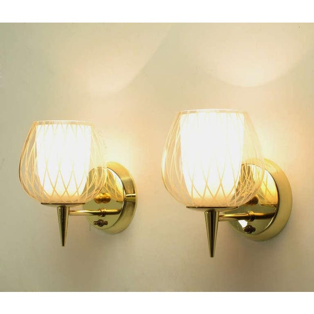 Pair of brass double hurricane sconces by Gerald Thurston for Lightolier. Each solid brass sconce has a double hurricane...