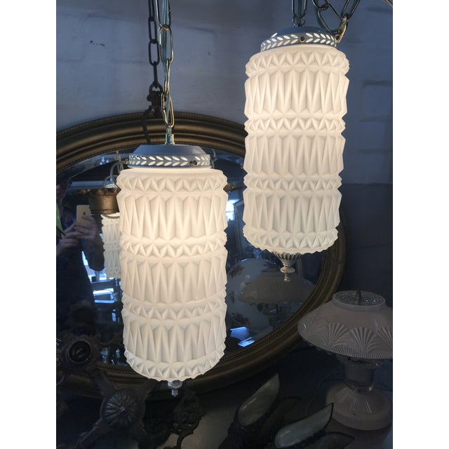 Mid-century modern pendant swag lights. White glass shades. A rare opportunity to buy two of these unique and stylish...