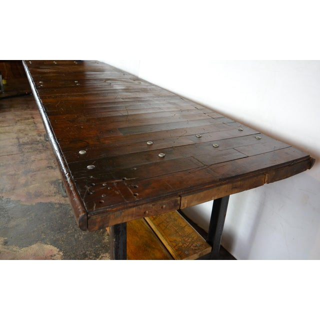 This is a huge, almost 10 ft long industrial table. Steel legs and fittings with a multi-plank top and under-shelf. Great...