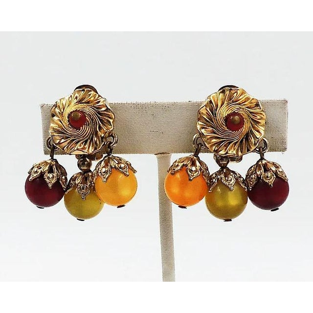 "Late 1950s or 1960s goldtone red, green and yellow moonglow dangle clip back earrings. Marked ""Napier."" Condition: Very..."