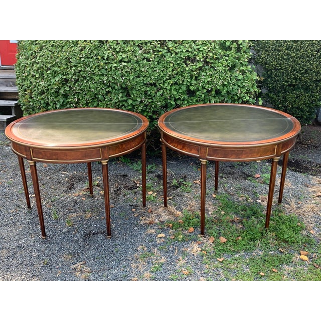 A stunning pair of crotch mahogany and brass demilunes that open to become round leather topped game tables. The brass...