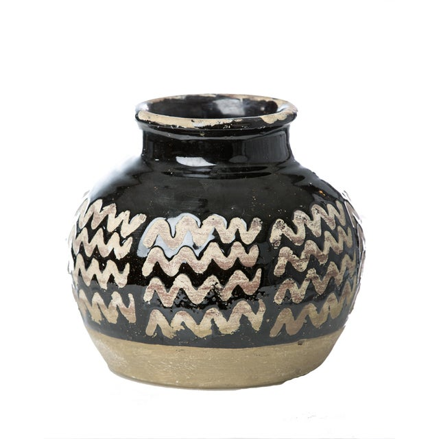 The distinct zig zag pattern on this low vase gives it a very geometric appeal, sure to blend in just about any space. Try...