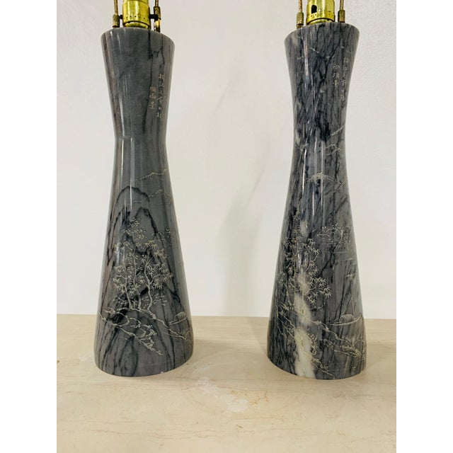 Pair of Etched Asian Themed Marble Lamps. The lamps have an etched, outdoor Asian scenery theme. Measures: 31.5H (top of...