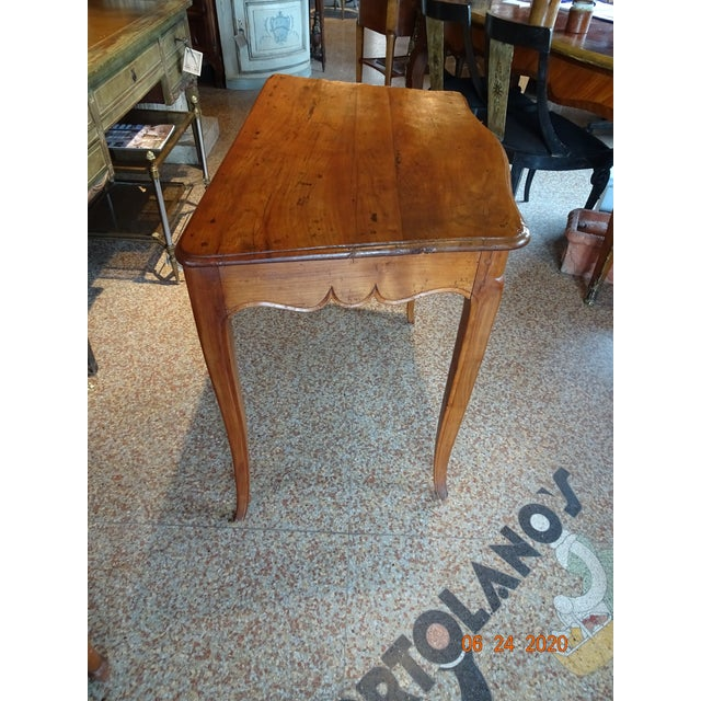 Charming 18th Century French table with a scrolled apron on three sides ( not the back ) and tapered curved legs....