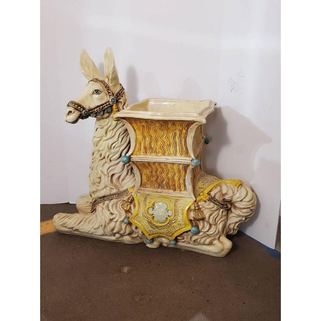 Painted ceramic figural indoor planter in the shape of a resting llama. Painted in shades of ivory and warm yellow with...
