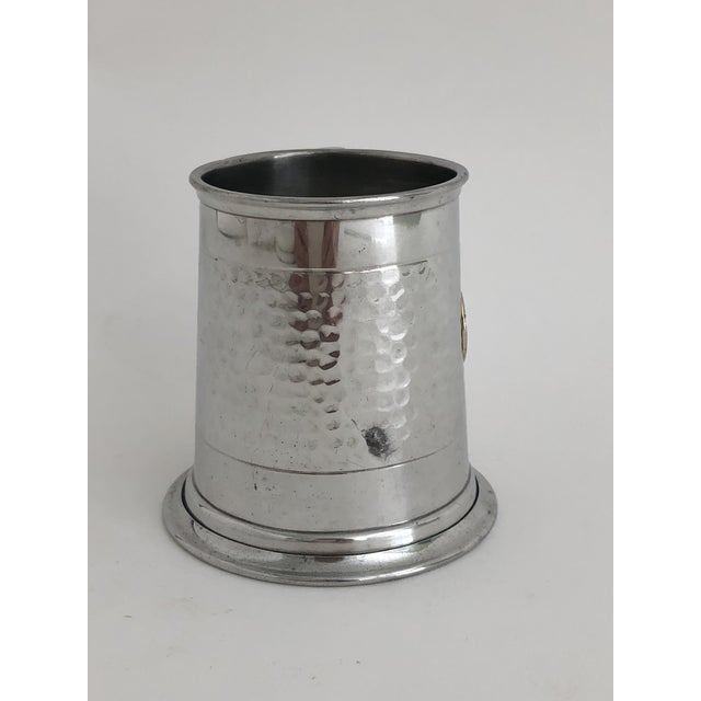 A commemorative hammered pewter mug with the insignia for Queen Elizabeth in an enamel seal. Marked Sheffield England. A...