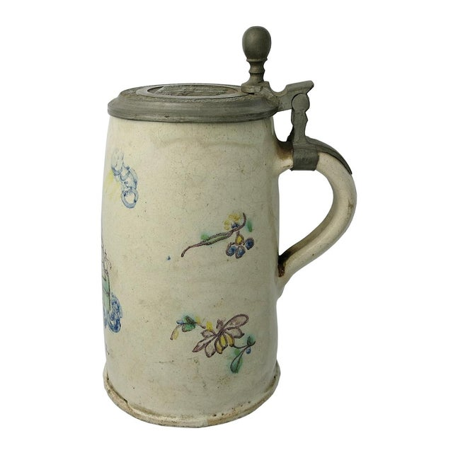 An Eighteenth Century German faience tankard. The tankard with a peter lid with a castle in relief and the body painted...