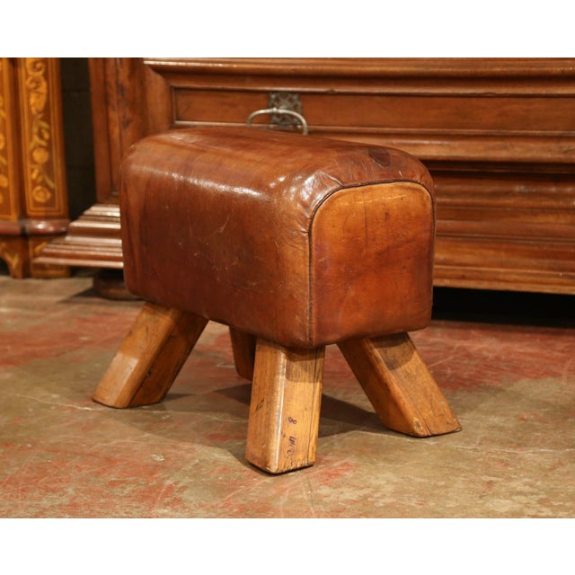 This antique, leather pommel horse bench was crafted in the Czech Republic, circa 1920. The rustic stool features four...