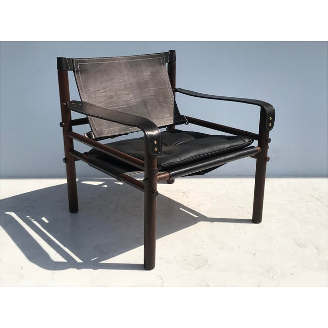 """Pair of Arne Norell black leather """"Sirocco"""" safari chairs in exotic tropical palm wood."""