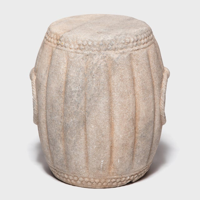 Hand carved of marble, this drum-shaped stool swells a ribbed melon shape, an ancient symbol of fertility. The artist used...