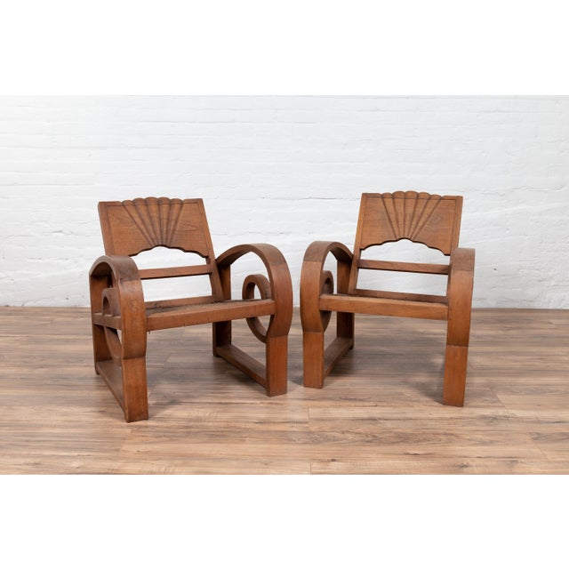 A pair of antique Indonesian teak wood country armchairs from Madura with rattan seats and looping arms. Born on the...