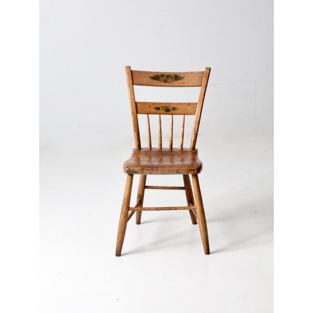This is an antique primitive chair circa late 19th century. The Hitchcock school wooden chair features a plank bottom seat...