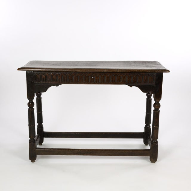 A 17th century joined oak side table, box stretchers, turned oak legs, finger groove carved apron and a single plank top,...